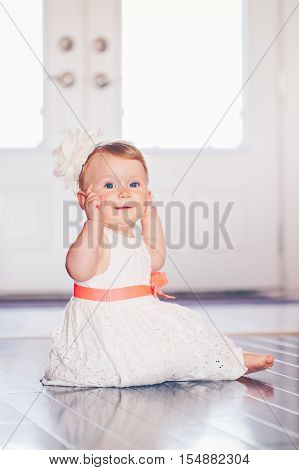 Portrait of cute adorable blonde Caucasian smiling baby child girl with blue eyes in white dress with red bow sitting on floor indoors looking in camera dreaming fairy tale sun light from above behind