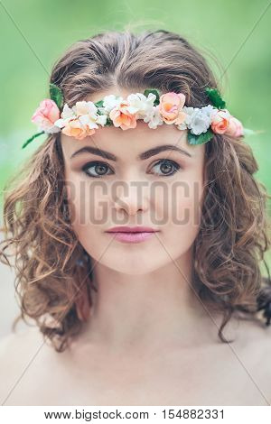 Closeup portrait of beautiful white Caucasian girl with hazel eyes long wavy curly hair and flowers chaplet on head. Attractive young woman model in park outside country village hippie style