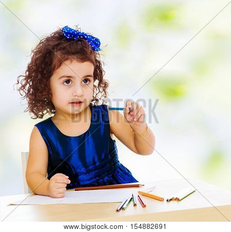 Pensive little girl in a blue dress, holding a pencil . She paints at a table in a Montessori kindergarten.white-green blurred abstract background with snowflakes.