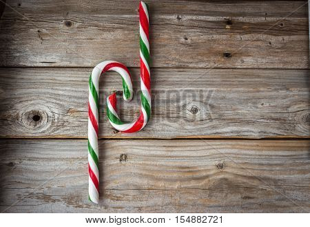 horizontal image of an old rustic wood background with two large candy canes intertwined on one side great for a greeting card idea,