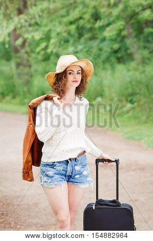 Portrait of beautiful Caucasian young girl woman in white sweater blue denim shorts straw hat standing with travel bag on the wild country road in forest looking in camera wanderlust adventure vacation