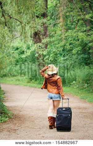 Portrait of Caucasian girl woman in leather jacket blue denim shorts straw hat standing walking on country road wild forest with travel bag with her back to camera wanderlust adventure vacation