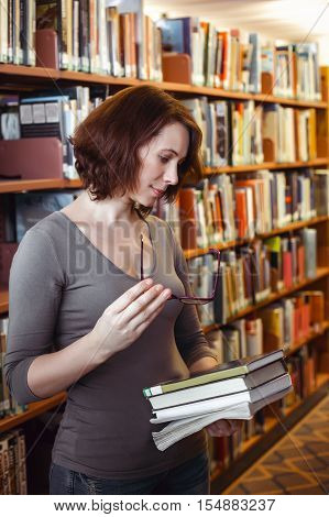 Portrait of middle age mature brunette Caucasian woman student with glasses in library holding book looking away from camera teacher librarian profession back to school concept