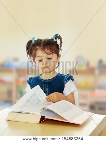 Pretty little girl in blue denim dress reading a book sitting at the table.In the Montessori room the children's garden where there are shelves with toys and material.