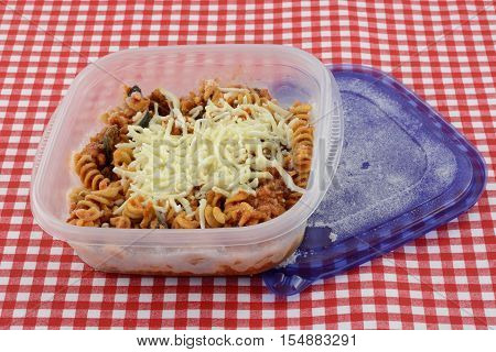 Frozen casserole portion in open plastic container on red and white tablecloth