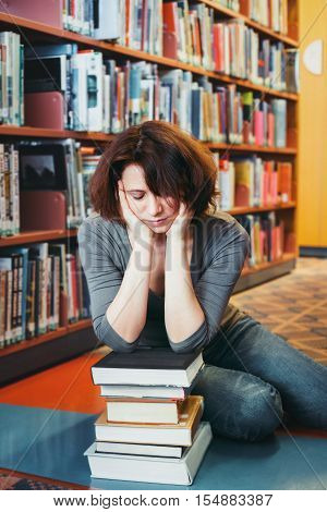 Portrait of tired middle age mature woman student sitting in library face in her arms sleeping teacher librarian profession back to school concept