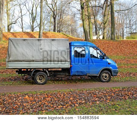 Old blue truck with body covered tarpaulin near path in autumn garden among fallen leaves which are raked up in heaps. Leaves will be put in the car and taken away for further processing.