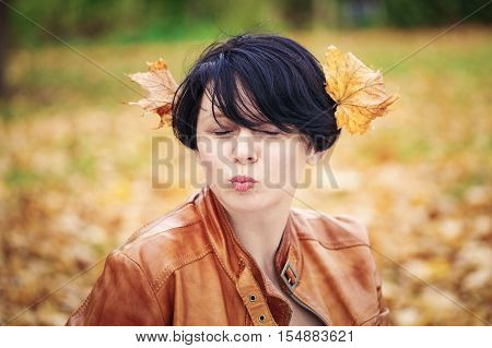 Closeup portrait of middle aged caucasian dark haired brunette woman with short bob hairstyle in light brown leather jacket her eyes closed outside in autumn fall park with leaves in her hair funny duckface