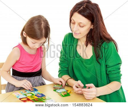 Cute little girl and her mother at the table laid out cards with pictures.Isolated on white background.