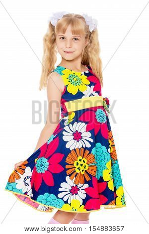 Beautiful little girl with long blonde ponytails on the head and white bows in bright summer dress keeps the dress over the edge