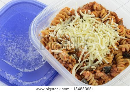 Close up of frozen casserole portion in plastic container on white background