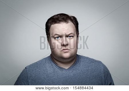 Close-up portrait of white Caucasian big fat stout man with blue eyes looking directly in camera in studio on light background sceptical suspicious expression emotion