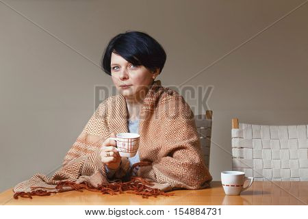 Portrait of beautiful Caucasian brunette mid age woman covered with blanket sitting at table drinking tea coffee holding cup in hands looking directly in camera waiting for somebody end of day evening night