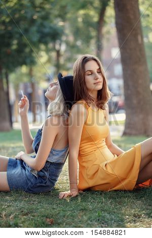 Portrait of two white Caucasian unformal young girls hipster students friends sitting ob grass outside in park on summer day talking together smoking relaxing best friends forever