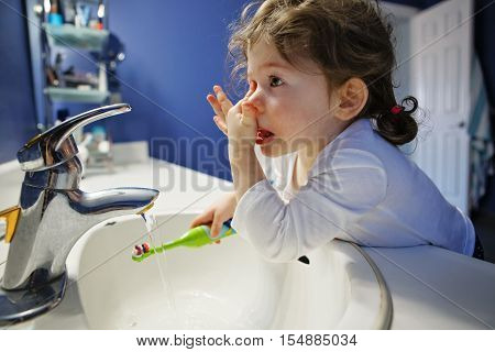 Closeup portrait of child toddler girl in bathroom toilet washing face hands brushing teeth with toothbrash playing with water lifestyle home style everyday moment morning routine