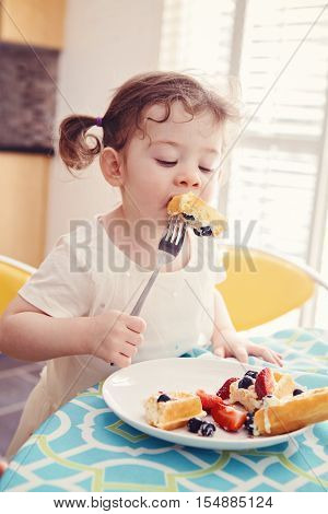 Portrait of one happy white Caucasian kid girl toddler with pig-tails in white dress eating breakfast waffles fruits with fork in sunny kitchen early morning
