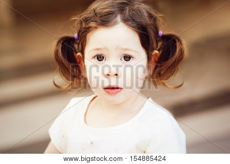 Closeup portrait of cute adorable sad upset white Caucasian toddler girl child with dark brown eyes and curly pig-tails hair in white light dress tshirt looking in camera