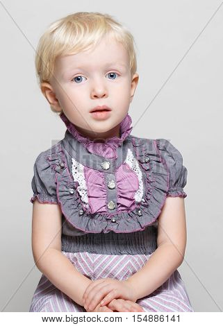 Closeup portrait of cute child toddler girl with blonde hair and blue eyes in vintage retro victorian gothic dress posing sitting in studio looking in camera light white pure plain background halloween concept