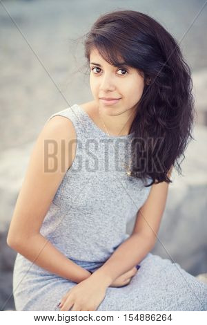 Portrait of beautiful Hispanic latino white girl woman with brown eyes long dark curly wavy hair in gray dress sitting in park outside smiling laughing looking in camera lifestyle portrait concept