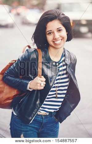 Portrait of beautiful smiling young Caucasian latin girl woman with dark brown eyes short dark hair in blue jeans leather biker jacket with backpack in city outside toned with filters