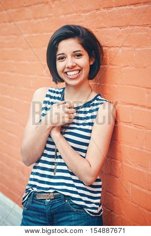 Portrait of beautiful smiling young hipster latin hispanic girl woman with short hair bob in blue jeans striped tshirt leaning on red brick wall in city looking in camera toned with filters