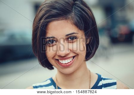 Closeup portrait of beautiful smiling young latin hispanic girl woman with short dark black hair bob black eyes outside looking in camera toned with  filters natural smile emotion