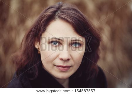Closeup portrait of beautiful middle age white caucasian brunette woman with green eyes in coat jacket on fall autumn day outside looking in camera on yellow rye background