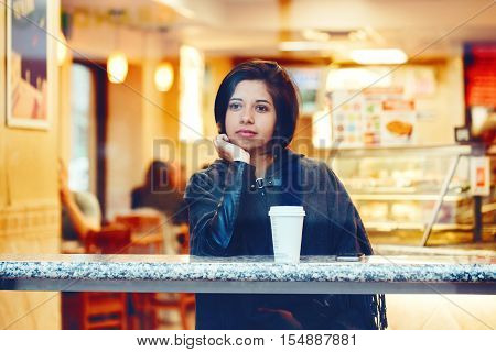 Candid portrait of beautiful young hipster latin hispanic girl woman with short hair bob in grey cape poncho jacket sitting in cafe restaurant with coffee looking away shot through window glass