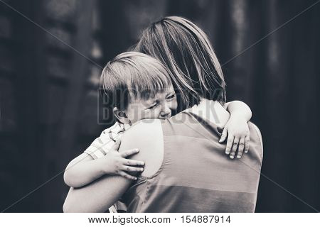 Black and white portrait of young Caucasian woman mother comforting her crying little toddler boy son outside in park on summer day parenthood lifestyle concept