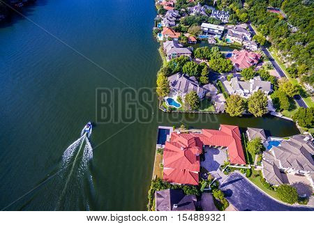 Aerial Drone View over Colorado River with Boat driving along town lake summer relaxation on the water. Mansions and Large houses line the side of the river with Colorful Rooftops in Austin , Texas