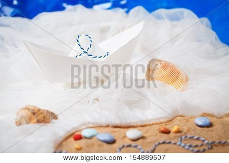 Still life closeup of paper boat origami toy in sea ocean waves with sand and rocks stones on the beach shore concept of traveling wanderlust adventure