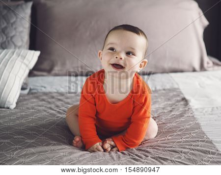 Portrait of cute adorable Caucasian smiling laughing baby boy girl with black brown eyes in orange red onesie shirt sitting on bed looking away from camera natural window light lifestyle