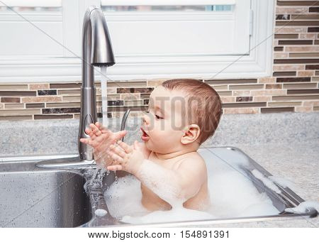 Portrait of cute Caucasian funny baby girl boy with dark black eyes sitting in big kitchen sink with water and foam near window looking away lifestyle everyday concept