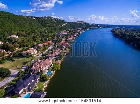 Over Colorado River at Mount Bonnell with Colorful mansions along the waters edge of Town Lake Austin Texas paradise Texas Hill Country