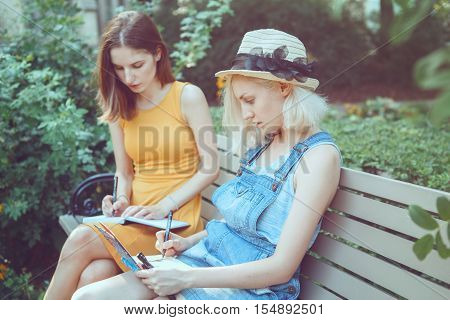 Portrait of two white Caucasian young girls hipster students friends outside in park on summer day sitting on bench together drawing sketching best friends forever toned with filters