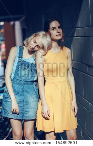 Portrait of two white Caucasian unformal young girls hipster students teenagers friends outside on summer day hugging together best friends forever