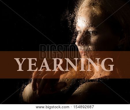 yearning written on virtual screen. hand of young woman melancholy and sad at the window in the rain.