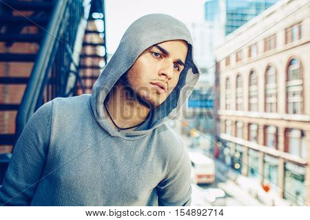 Conceptual art portrait of beautiful handsome gothic young middle east brunette man with blue eyes beard wearing blue grey hoodie outside in urban street looking away