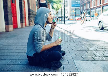 Conceptual art portrait of beautiful young middle east brunette man with beard wearing grey hoodie sitting on ground in street outside in city blowing soap bubbles having fun lifestyle