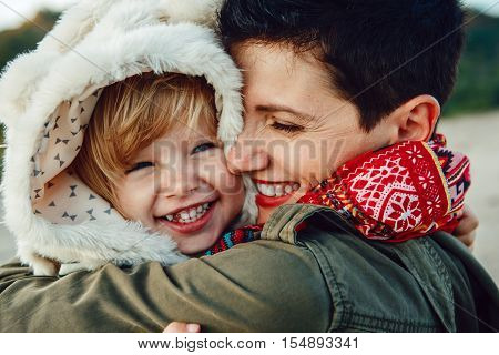 Closeup group portrait of white Caucasian mother and daughter baby girl hugging smiling laughing on sunset autumn fall winter season happy lifestyle childhood concept