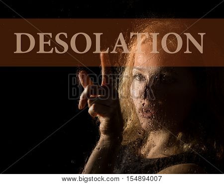 desolation written on virtual screen. hand of young woman melancholy and sad at the window in the rain