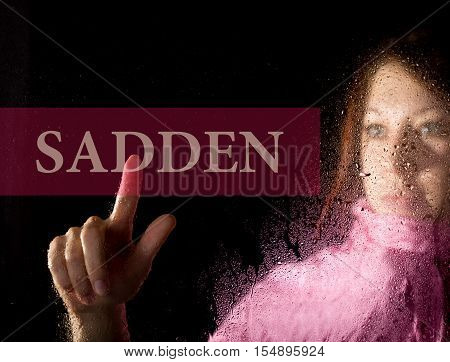 sadden written on virtual screen. young woman melancholy and sad at the window in the rain. her neck warm scarf