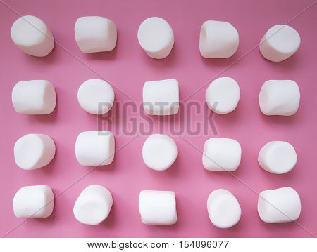 white marshmallows on a pink background. geometric pattern of white marshmallows. top view