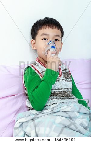 Sad asian child holds a mask vapor inhaler for treatment of asthma and looking at camera on sickbed in hospital. Breathing through a steam nebulizer. Concept of inhalation therapy apparatus.