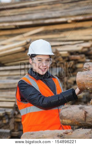 Lumber specialist at work with cut trees on the background