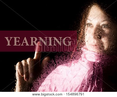 yearning written on virtual screen. young woman melancholy and sad at the window in the rain, her neck warm scarf.