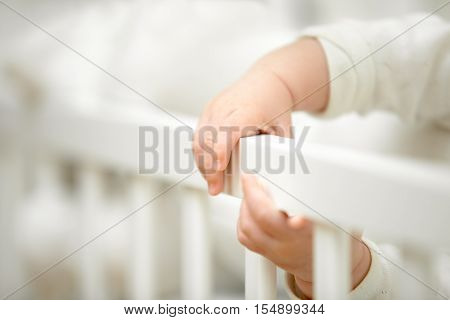 Infant tiny hands in the crib holding onto the side of the bed, have fun grabbing it. Closeup, baby development concept photo