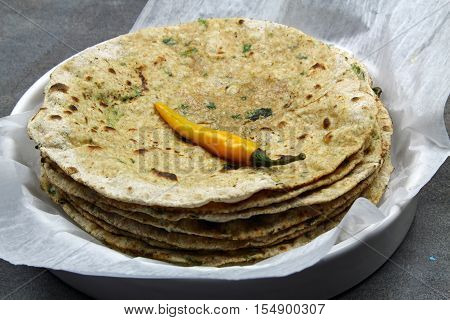 A stack of whole wheat and chopped spinach leaves Chapati or Roti or Tortilla with a hot chili pepper selective focus.
