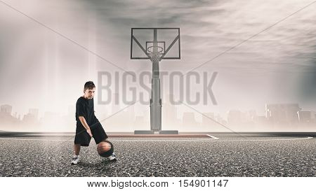 Kid challenging to play basketball on urban background.