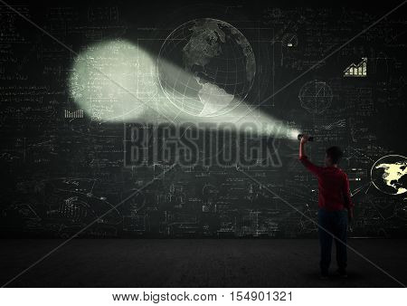 Kid using a flashlight in a dark room on a blackboard full of math formulas